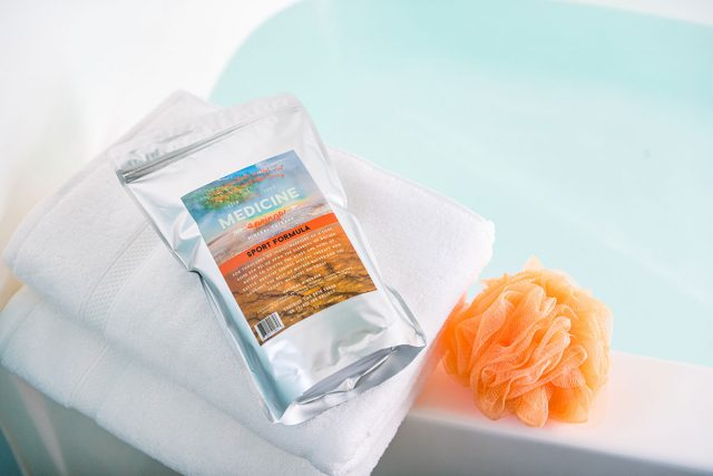 A pouch of Medicine Springs Sport Formula mineral therapy product next to a loofah sponge pouf