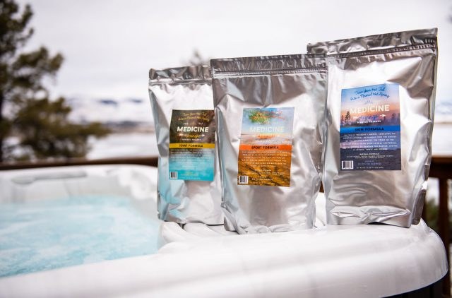Three pouches of Medicine Springs product. These are the Joint Formula, Sport Formula and Skin Formula mineral therapy sitting on the edge of a hot tub.