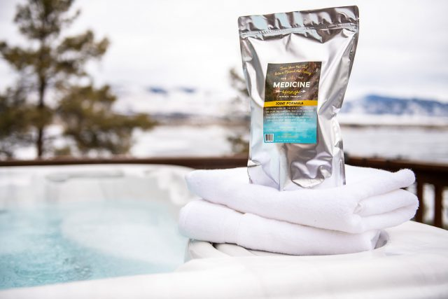 A pouch of Medicine Springs Joint Formula mineral therapy product sitting on the edge of a hot tub.