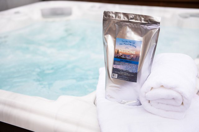 A pouch of Medicine Springs Skin Formula mineral therapy product sitting on the edge of a hot tub.