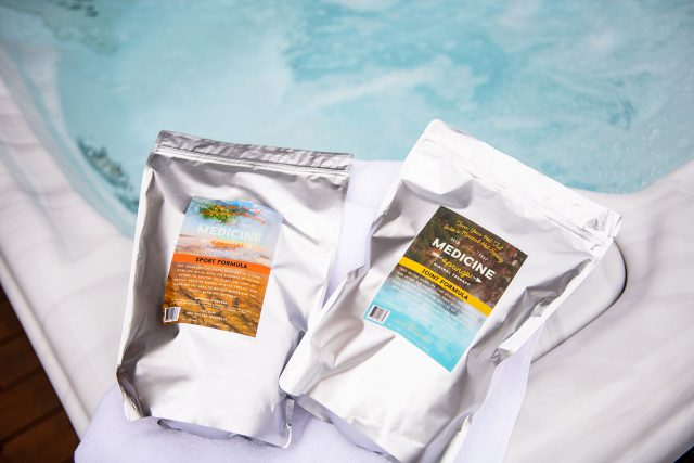 Two pouches of Medicine Springs product. These are the Sport Formula and Joint Formula mineral therapy sitting on the edge of a hot tub.